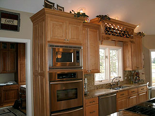 Cabinets fit to custom specifications to fit kitchen design with wine rack and lighting.
